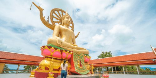 Woman standing in front of Big Buddha Statue in Koh Samui one of the Best Places in Thailand