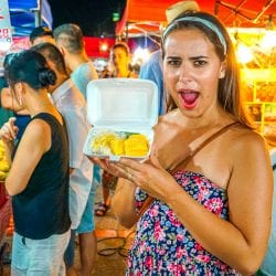 Girl holding up mango sticky rice in chiang mai Woman and Man hugging on Railay Beach West Thailand on Chase Your Adventure Tours