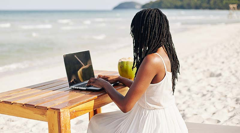 Woman teaching english online as a digital nomad on a beach