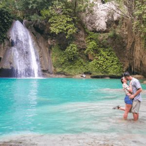 A couple kissing at Kawasan Falls in Cebu Philippines