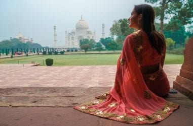 Woman in a saree sitting in front of the Taj Mahal