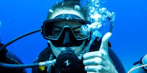 Girl Scuba diving giving a thumbs up