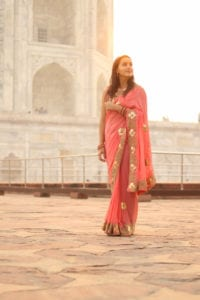 Woman in a saree in front of the Taj Mahal