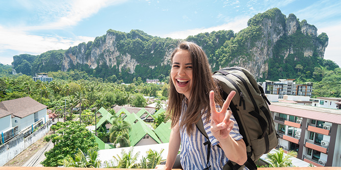 A full time traveler sitting on a balcony with a backpack in front of a mountain.